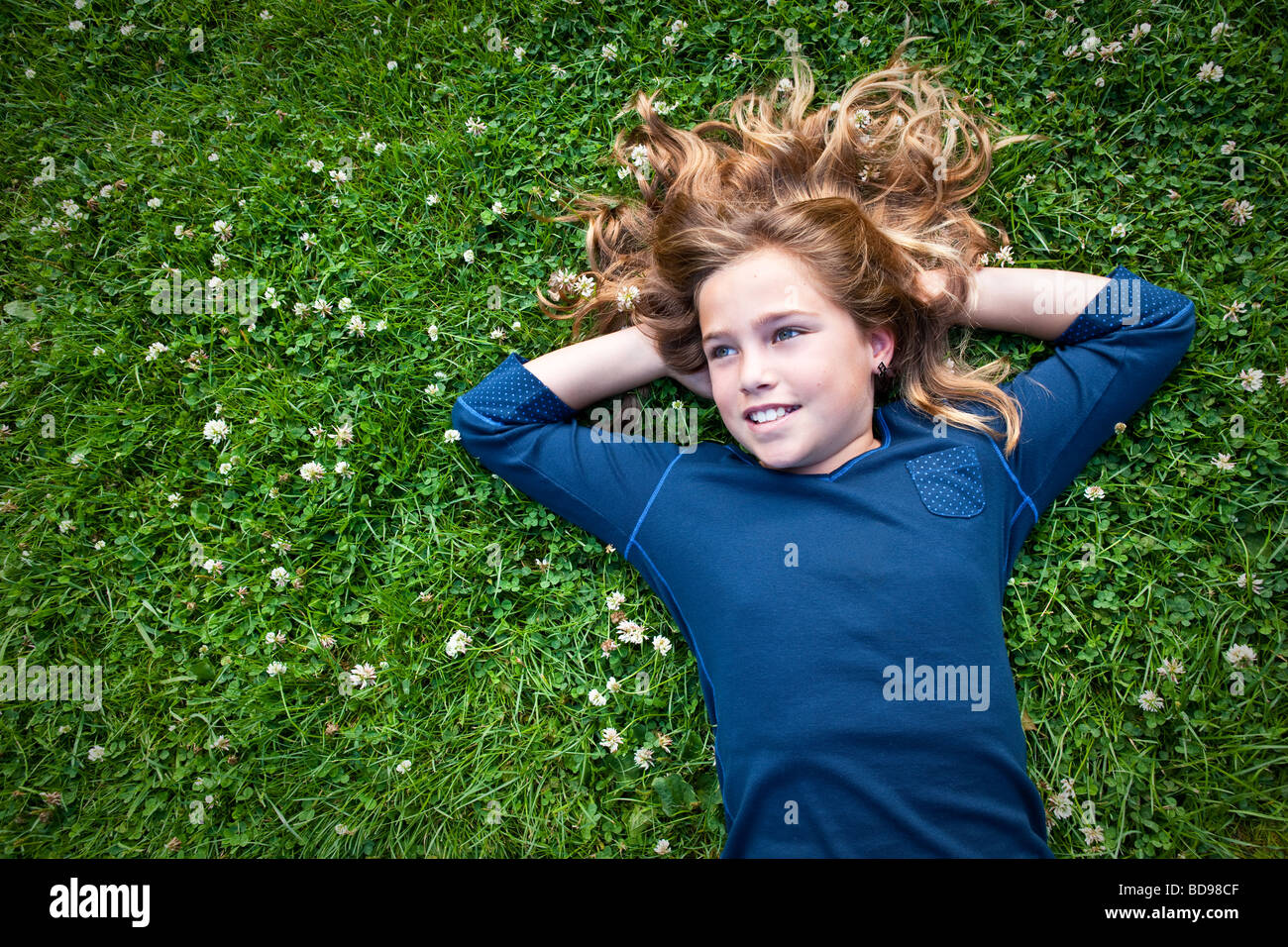 Girl 8-12 years old lies in a grassy field daydreaming - Stock Image