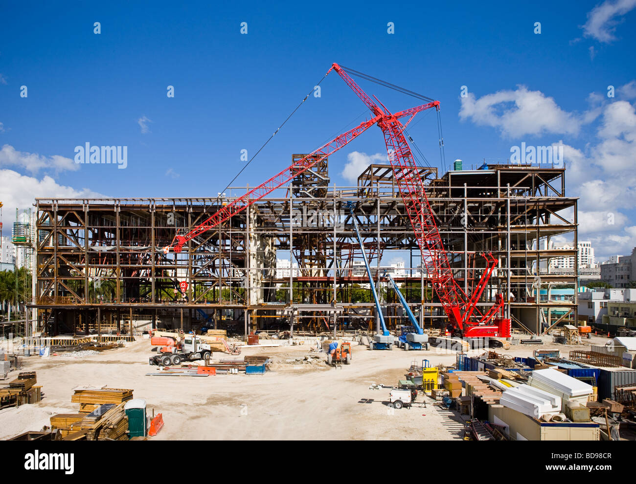 A construction site with blue sky and red crane. All logos, signs and other intellectual property have been digitally - Stock Image