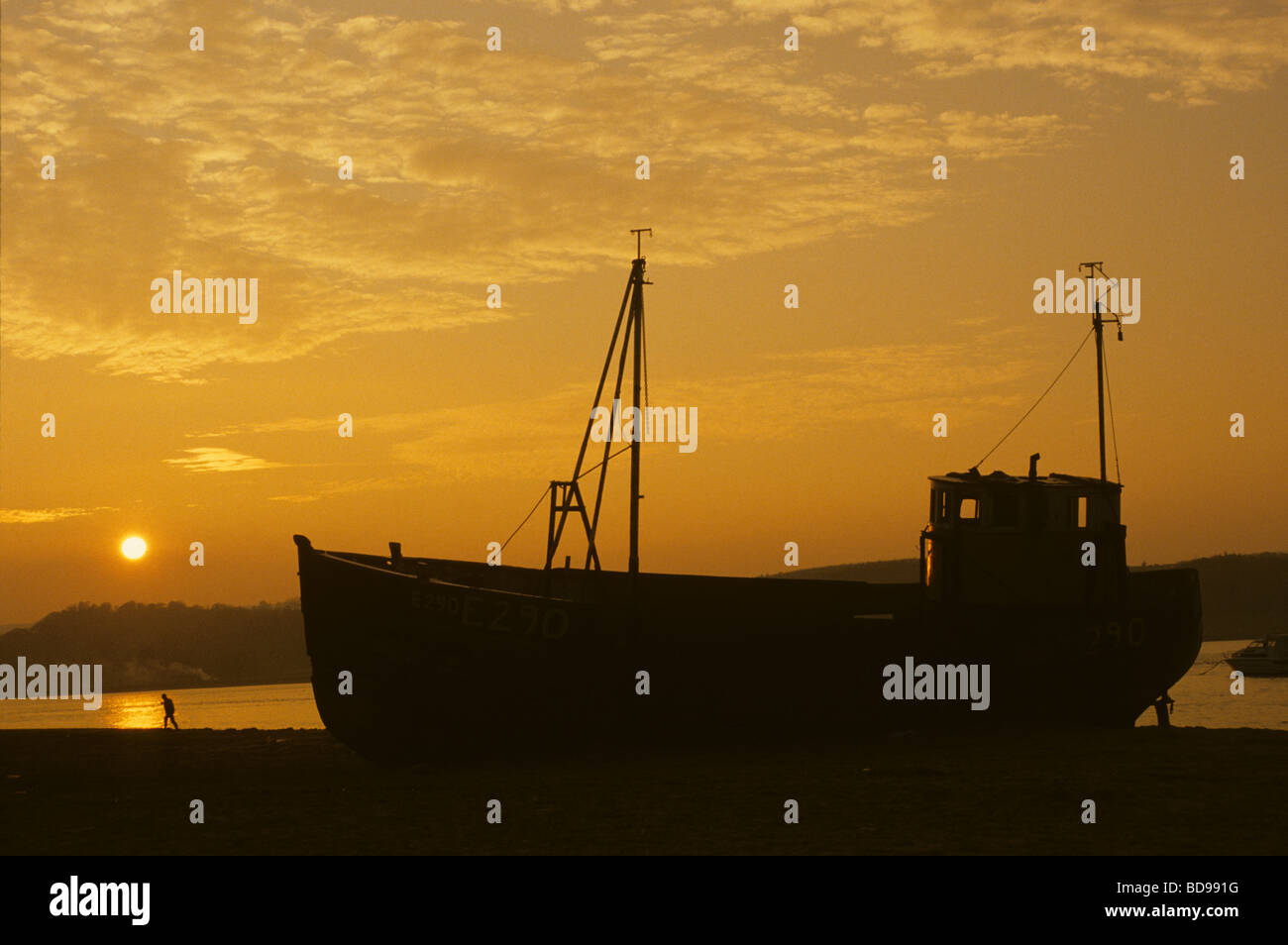 A beached fishing boat at sunset on the Exe estuary, Dawlish Warren, Devon, England - Stock Image