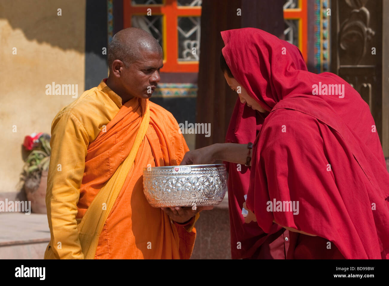 Bodhnath, Nepal.  A Buddhist Monk Receives an Offering from a Tibetan Monk in front of the Tamang Gompa (Monastery). - Stock Image