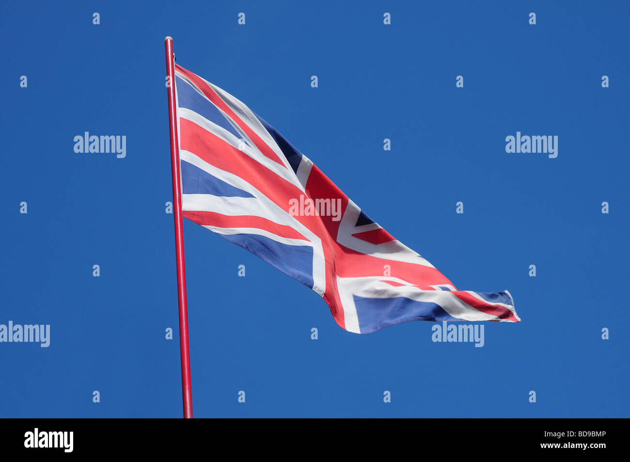 British Union Jack fluttering in a bright blue sky - Stock Image