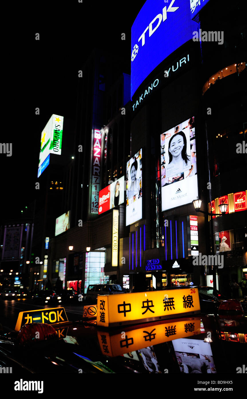 Taxi cab sign with advertisements screens in background in Ginza district Tokyo Japan Stock Photo