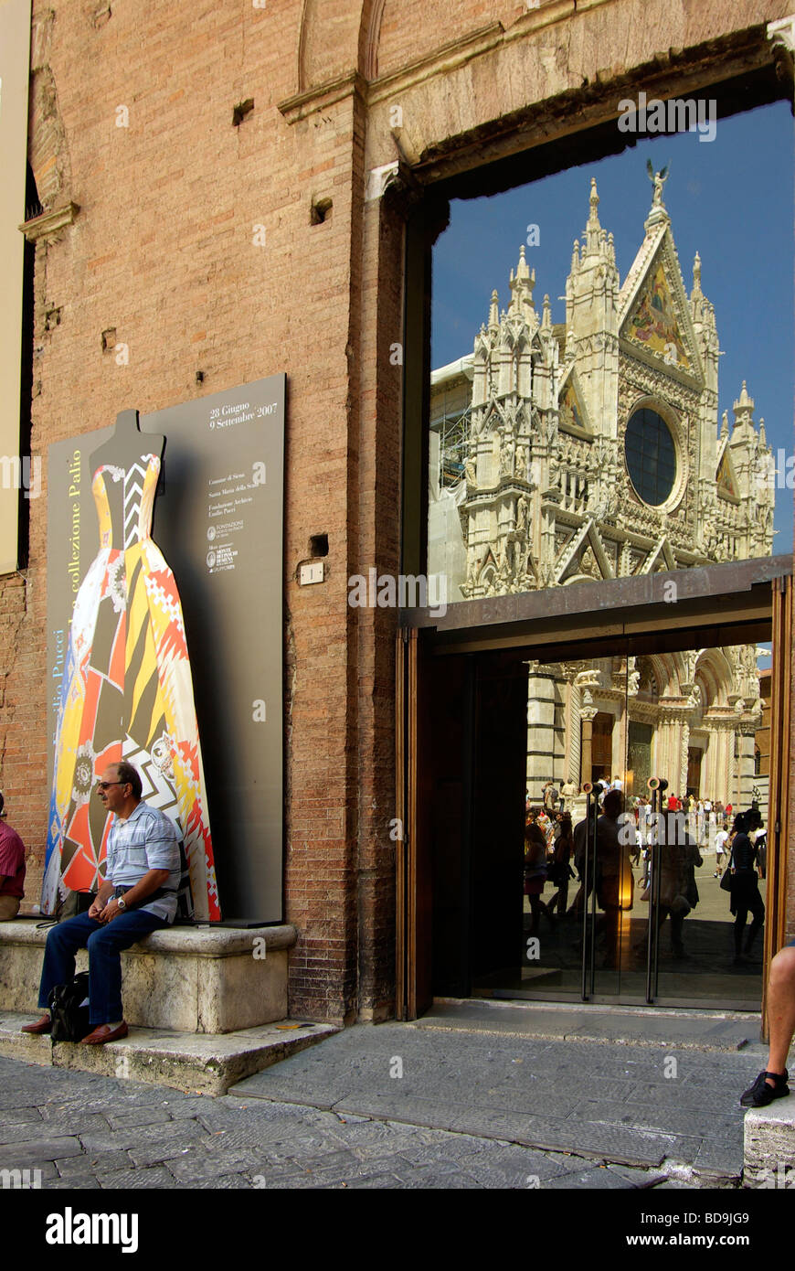 Tourist man sits in the shade outside the museum of Santa Maria della Scala with the Duomo (cathedral) reflected Stock Photo