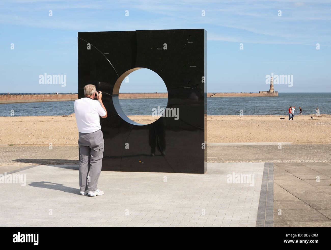 Man taking a photograph of Roker lighthouse through a monolithic granite structure aligned with the stars of the - Stock Image