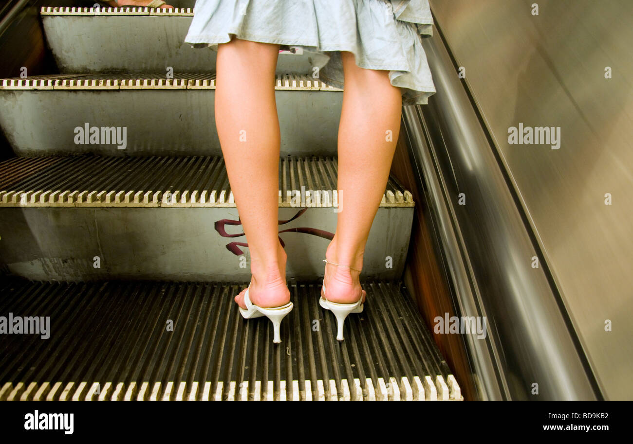 Budapest, Hungary. Woman with bowed legs on escalator in Metro - Stock Image