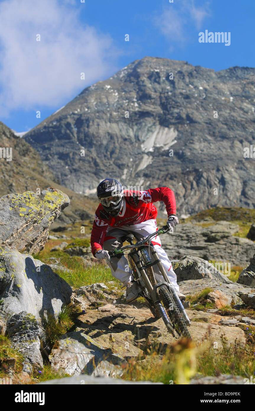A downhill mountain biker rides through rocks in the mountains in Les Arcs in the French Alps - Stock Image