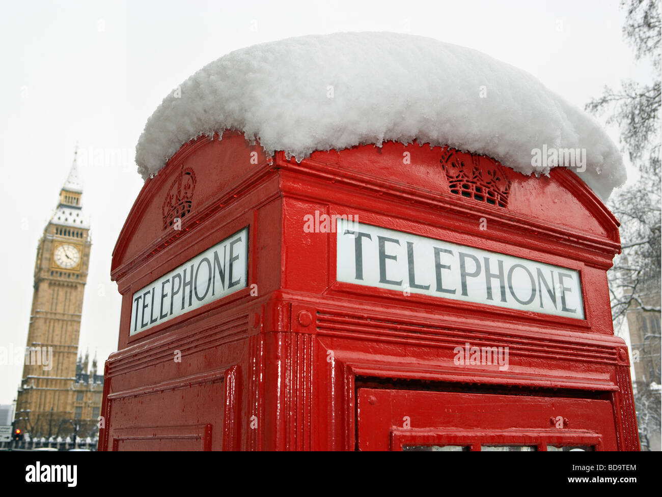 Snow on red telephone box and Big Ben London England - Stock Image