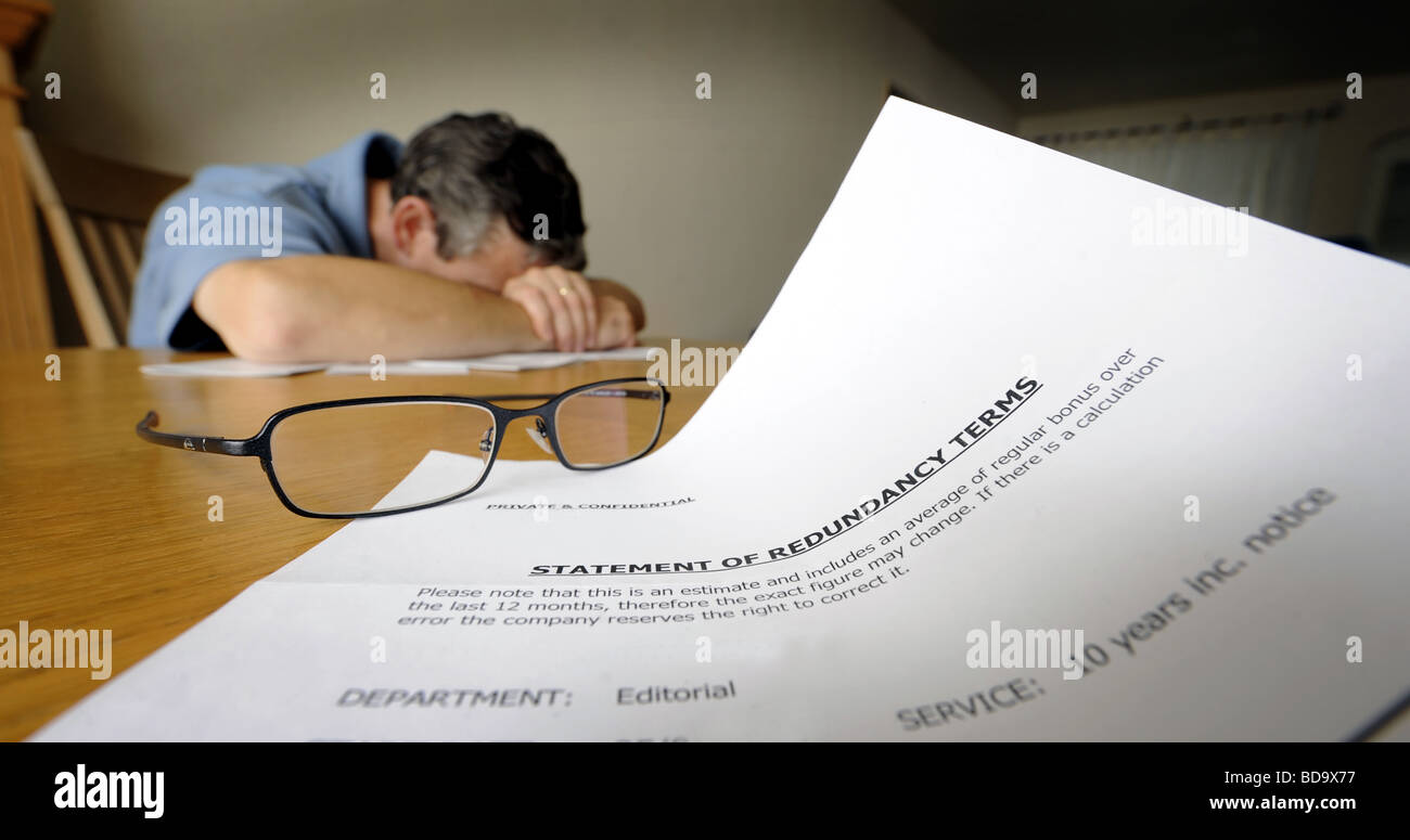 DISTRAUGHT MAN WITH REDUNDANCY LETTER SHOWING STATEMENT  OF TERMS UK. - Stock Image