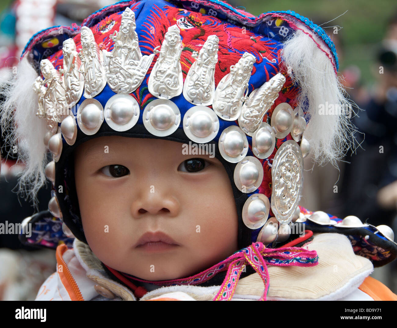 Close up Miao baby with ornate headdress Drum Festival Shidong Guizhou Province China - Stock Image