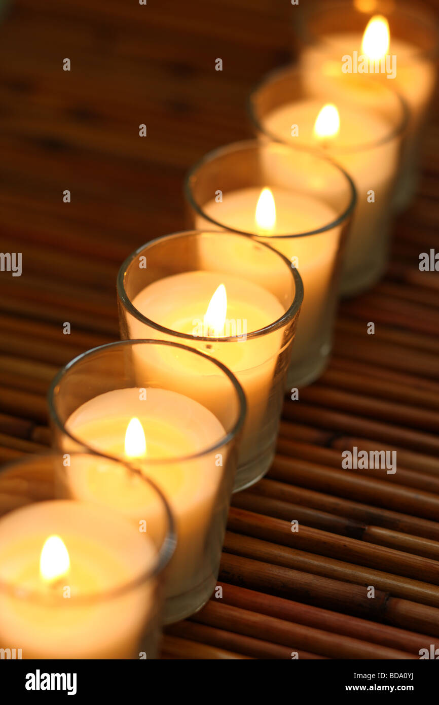 Row of candles on bamboo background - Stock Image