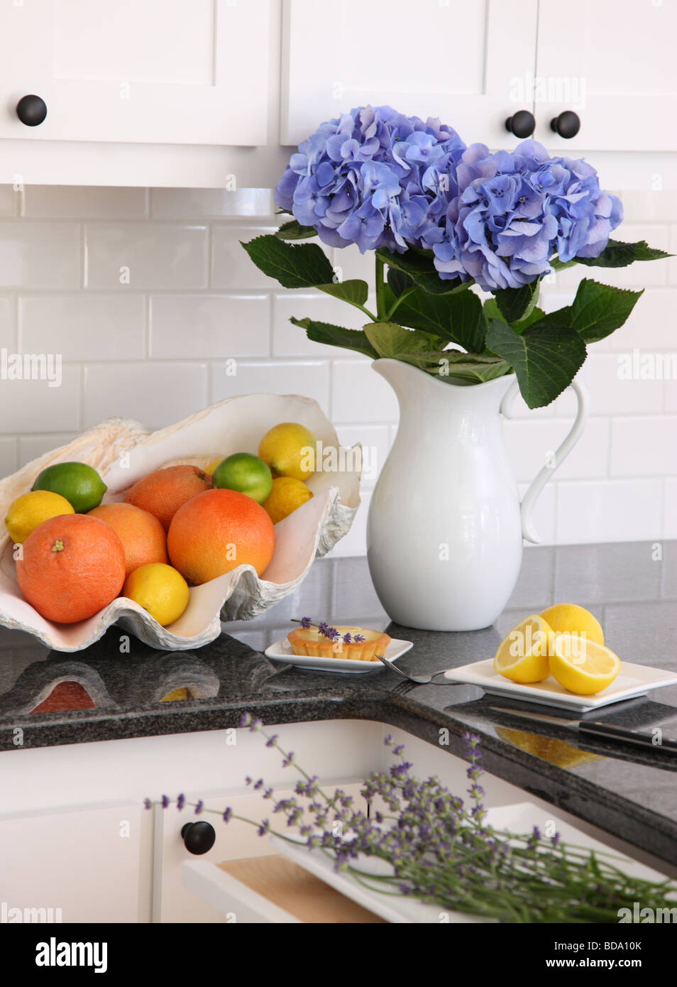 Kitchen still life with citrus fruit and flowers - Stock Image