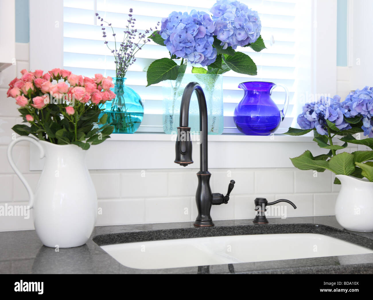 Kitchen sink with flowers - Stock Image