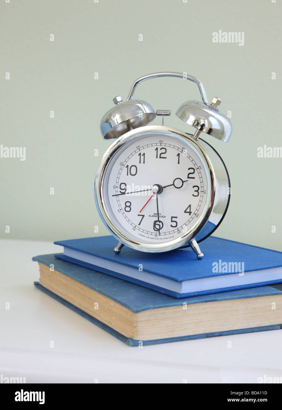 Alarm clock on stack of books - Stock Image