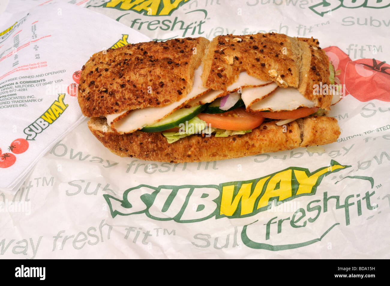 Subway turkey sub sandwich with cucumber lettuce tomato and onion on wrapper with logo USA. - Stock Image