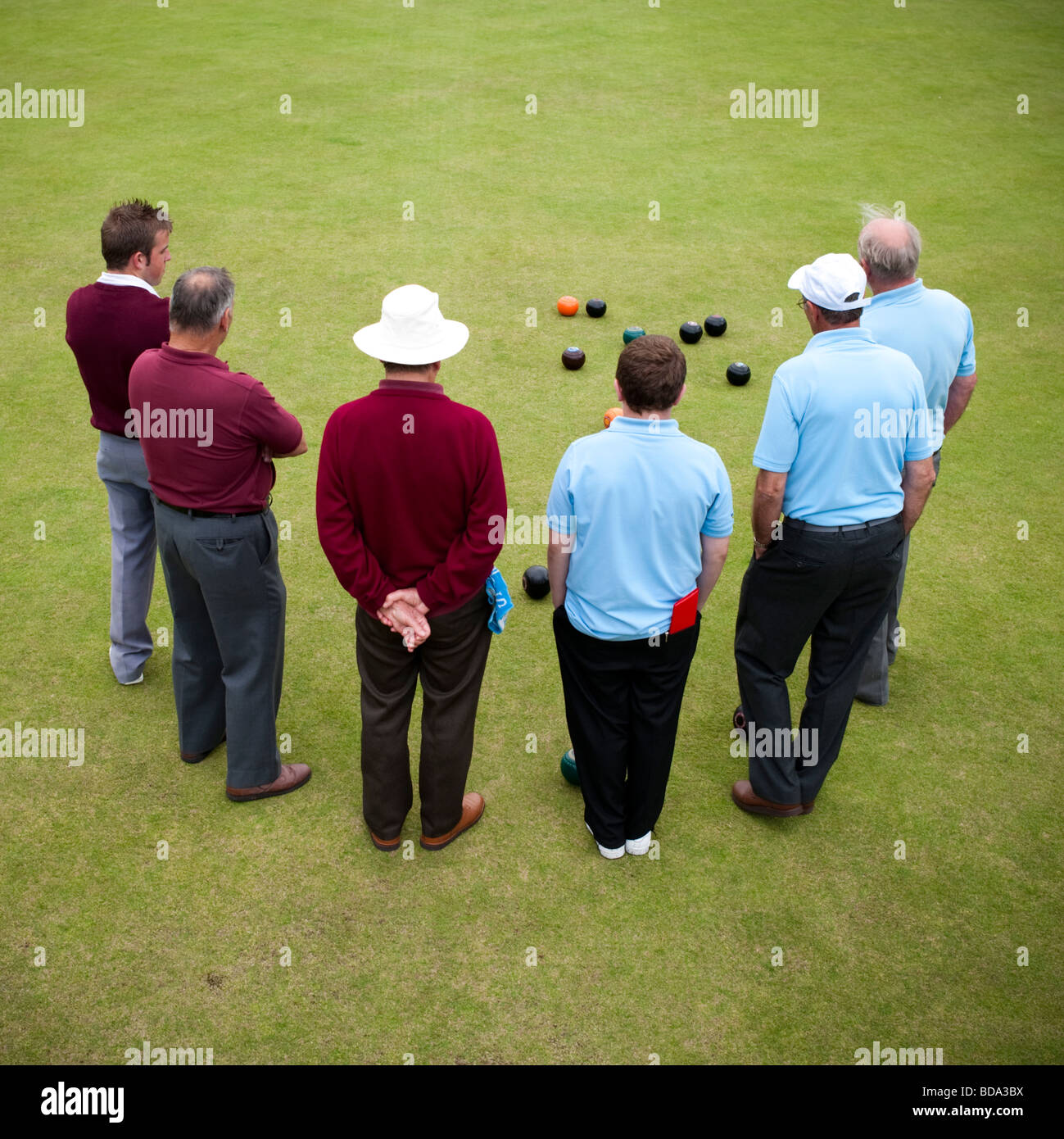 Rear view of 6 men standing in an arc, playing lawn bowls Aberystwyth Wales UK - Stock Image