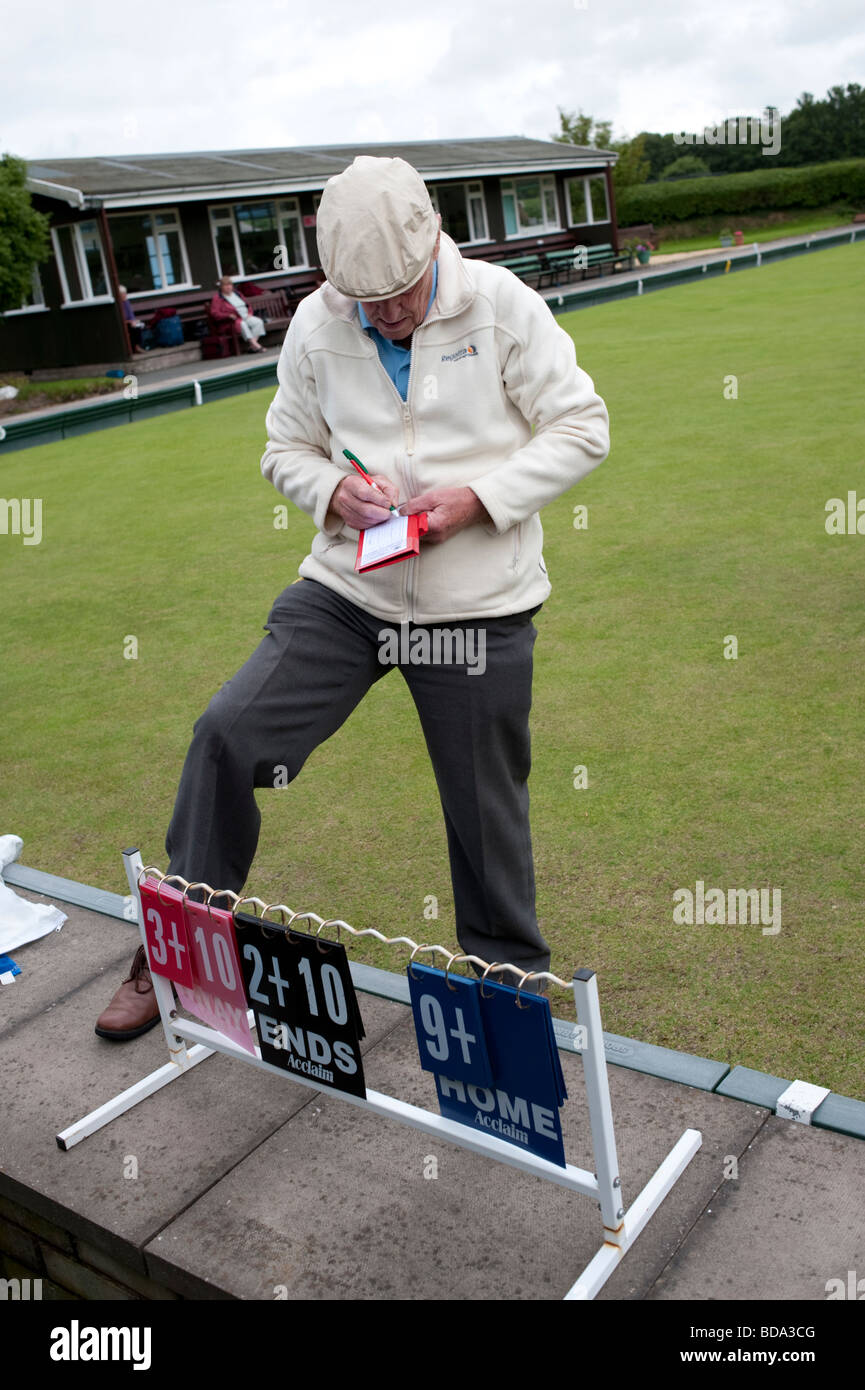 An elderly man writing the scores on a scorecard after a game of lawn bowls Aberystwyth Wales UK - Stock Image