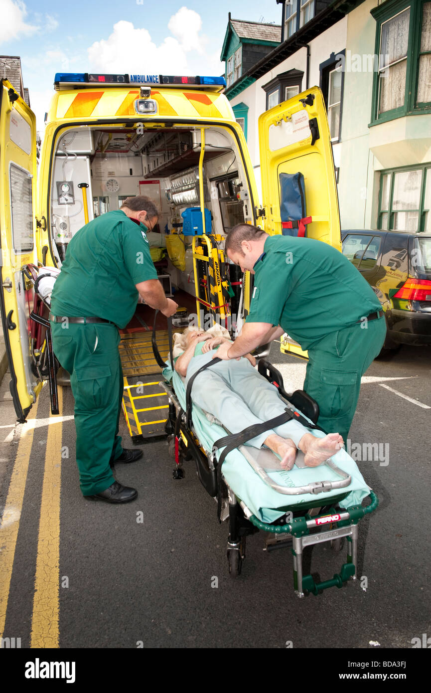 Paramedics responding to a 999 call putting elderly lady who has fallen over at home on a stretcher and taking her - Stock Image