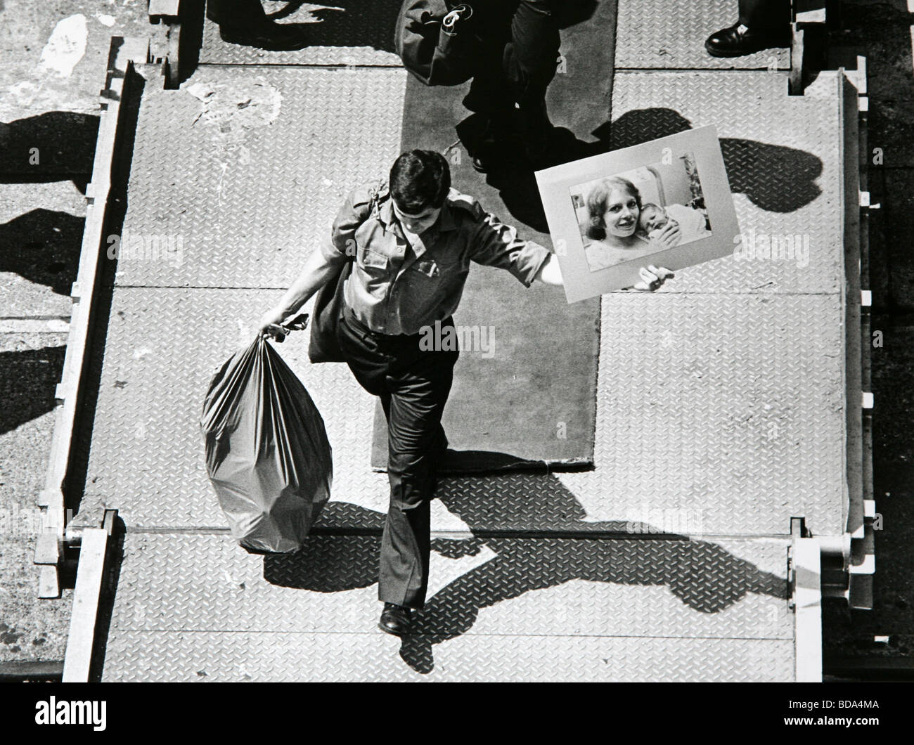 A serviceman returning from the Falklands War walks off the QE2 in Southampton with a photograph of his wife and - Stock Image