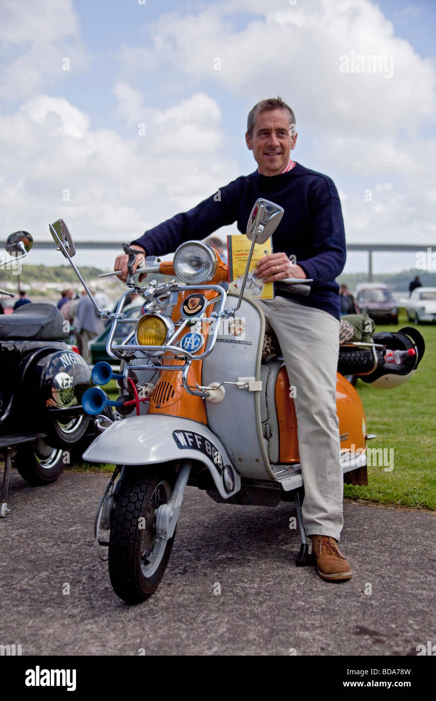 Man on Original orange and Grey Lambretta 1960's motor cycle in show with Chromes, Klaxon, mirrors headlights. - Stock Image