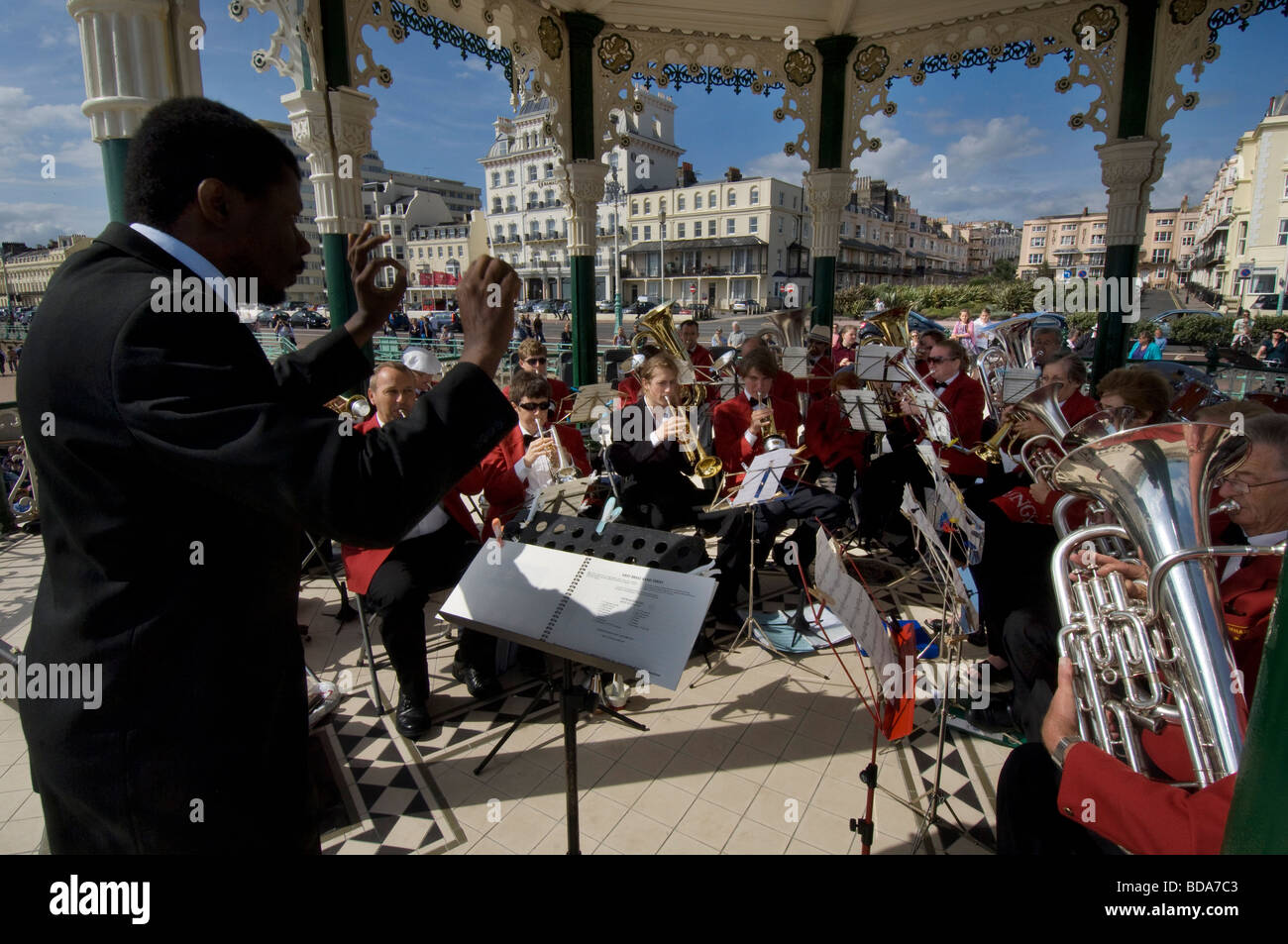 A black conductor leads the Patcham silver band in a concert on Brighton bandstand - Stock Image