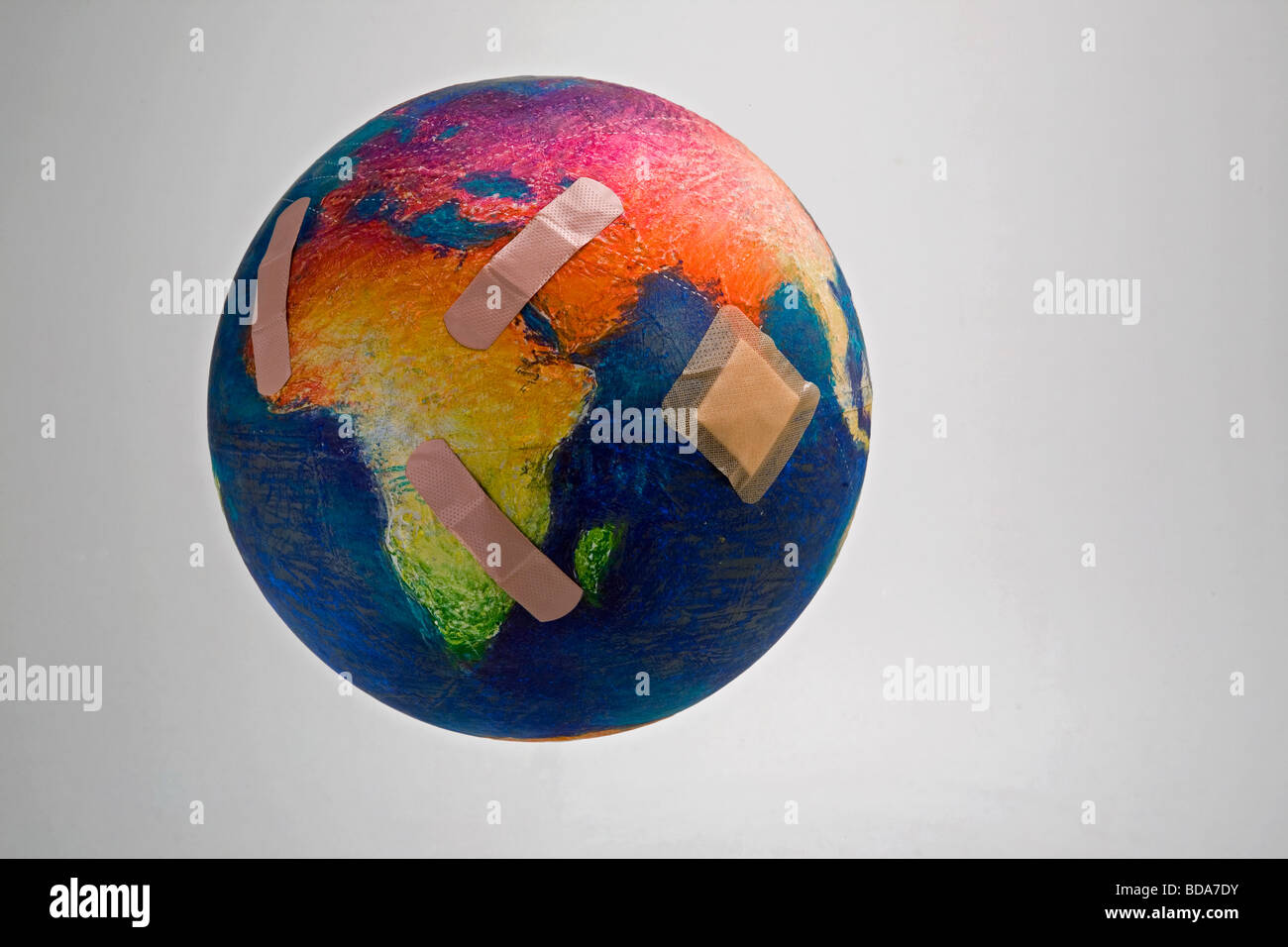 Still shot of a world globe with band aids on Africa and Asia - Stock Image