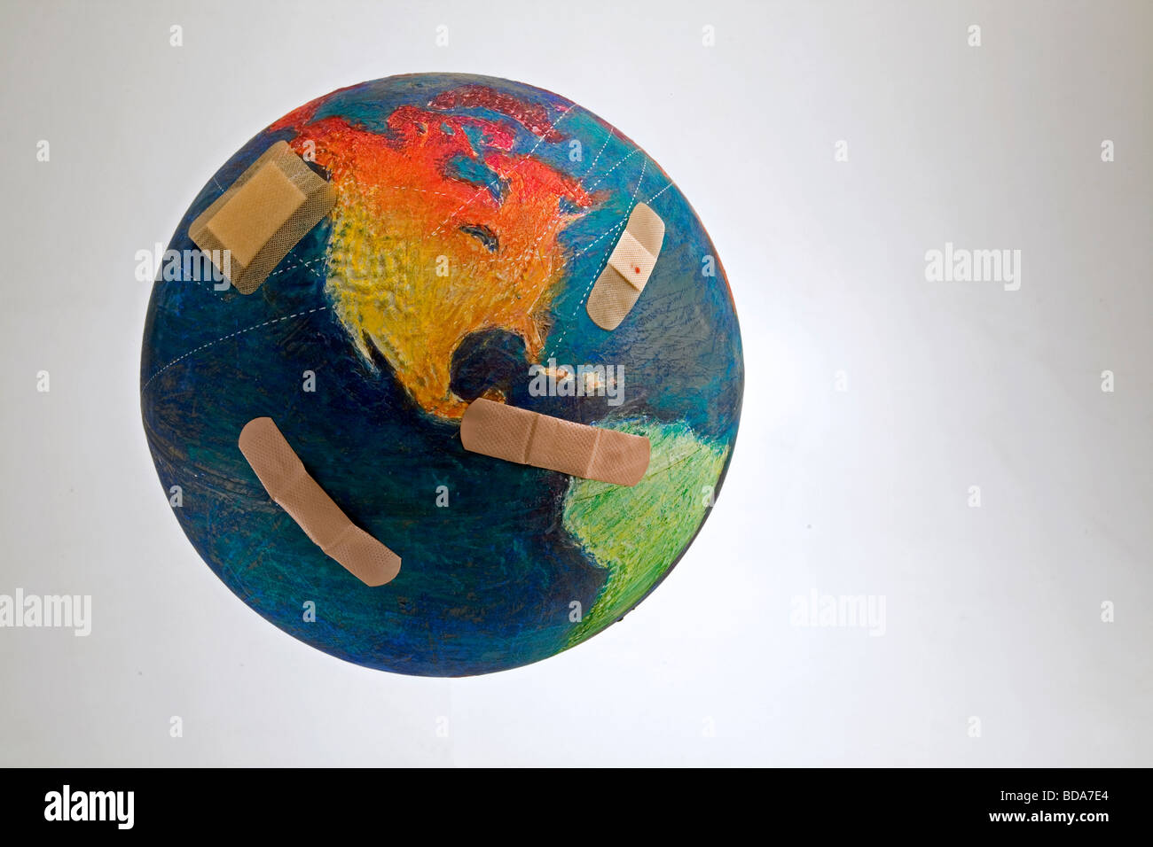 Still shot of a world globe with band aids on the Oceans and Central America - Stock Image