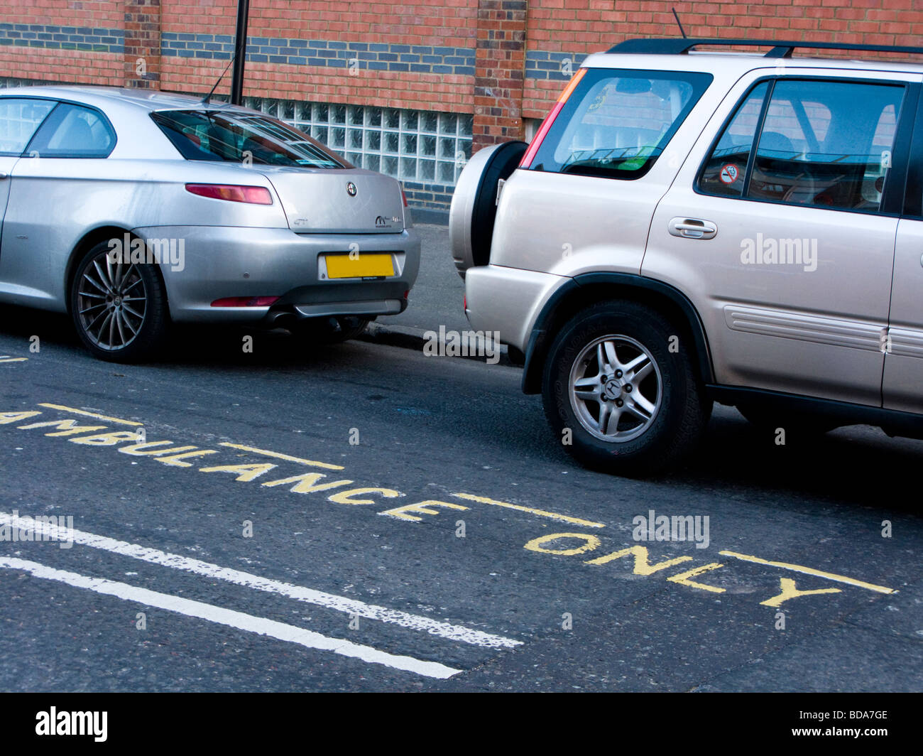 Two cars parked on Ambulance Only bay, London, UK - Stock Image