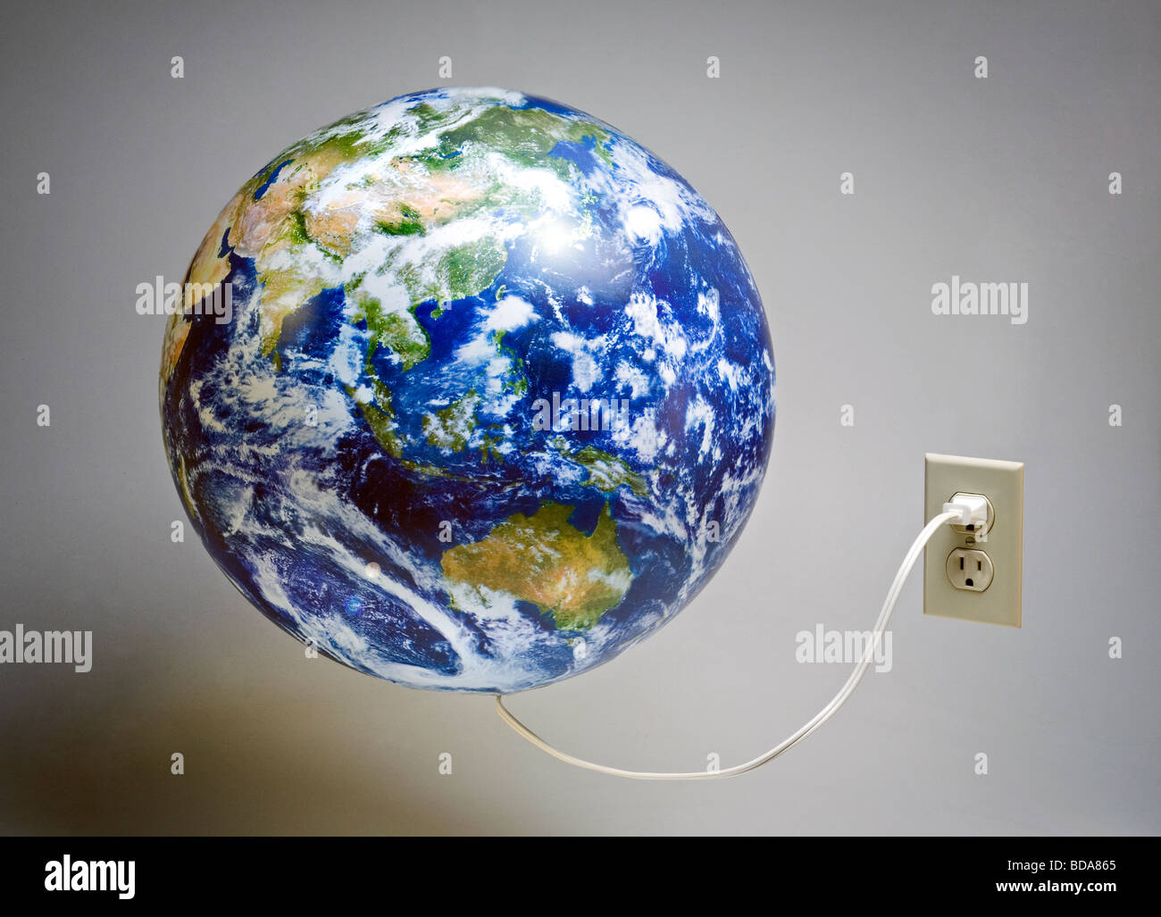 Still shot of a world globe plugged into an electrical outlet - Stock Image