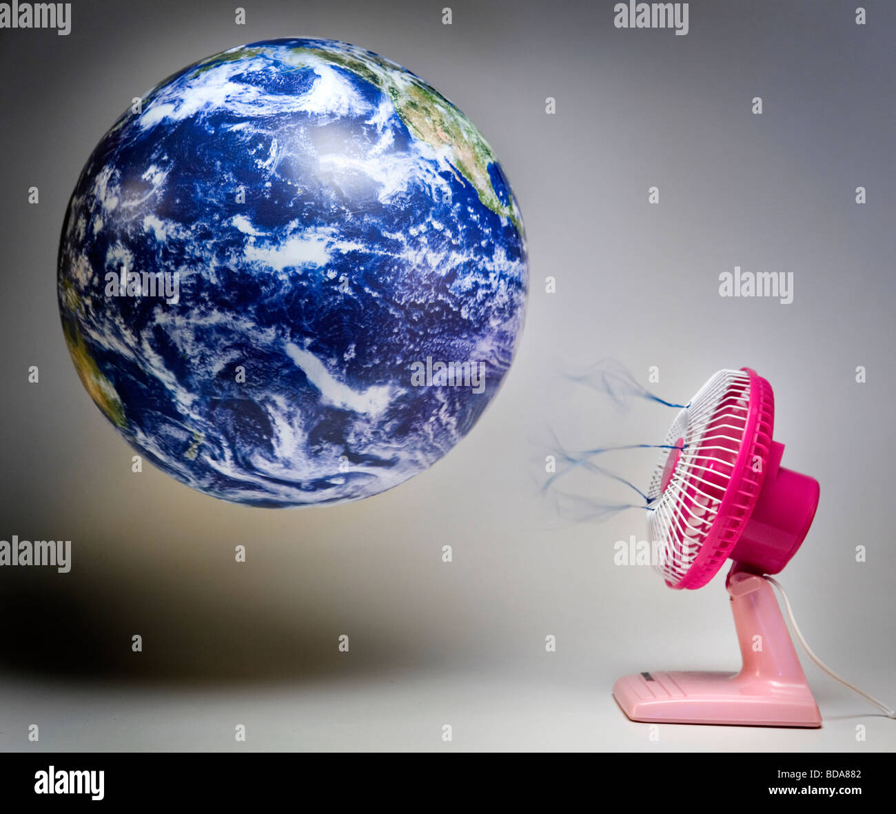 Still shot of a world globe with a pink fan blowing air on it - Stock Image