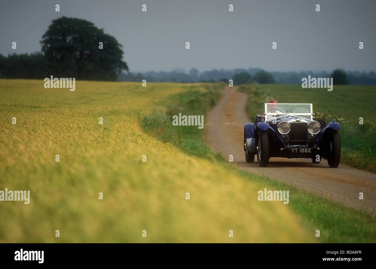 1930 s Invicta car driving down an English country lane - Stock Image