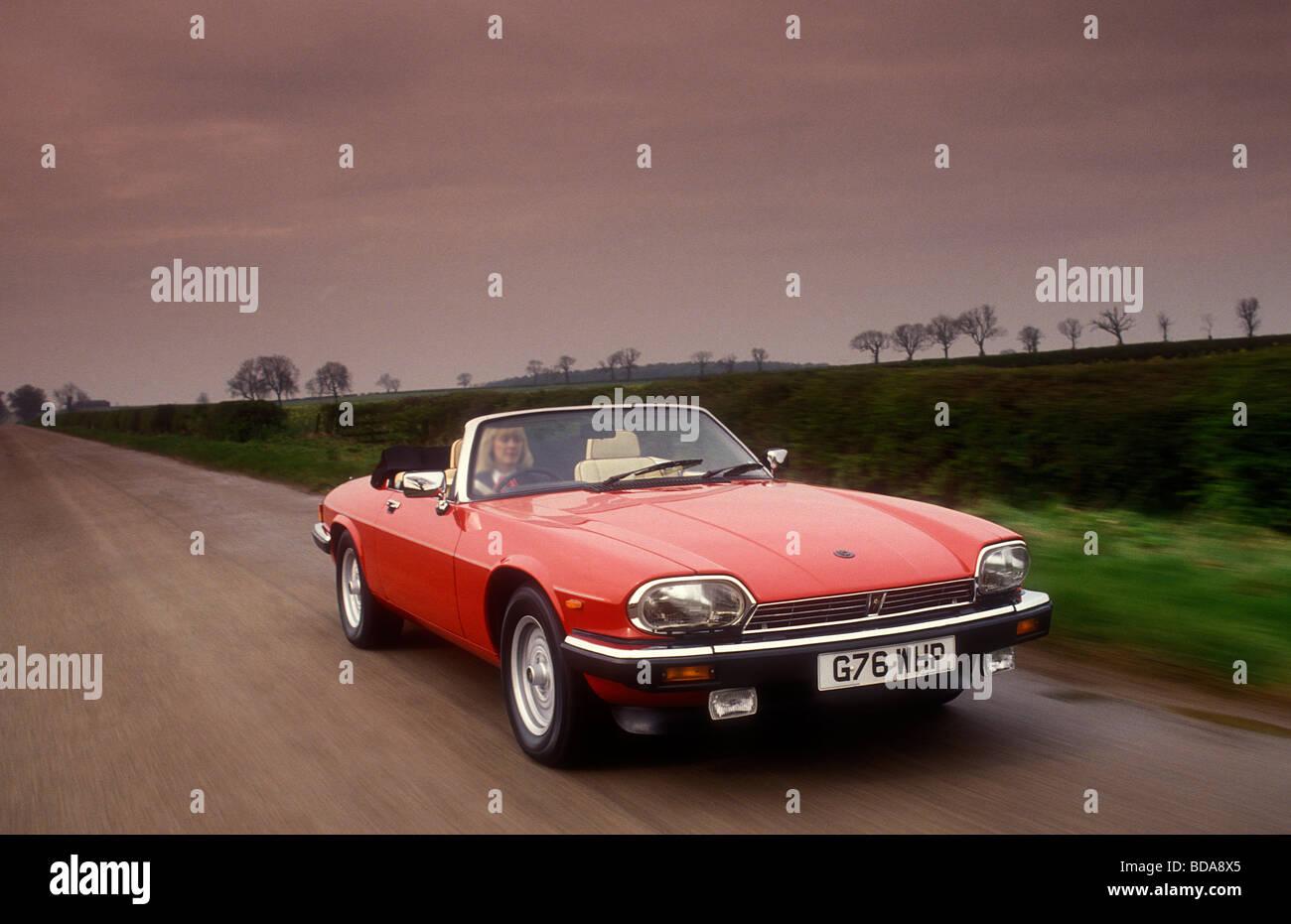 Jaguar XJS driving down English country road - Stock Image