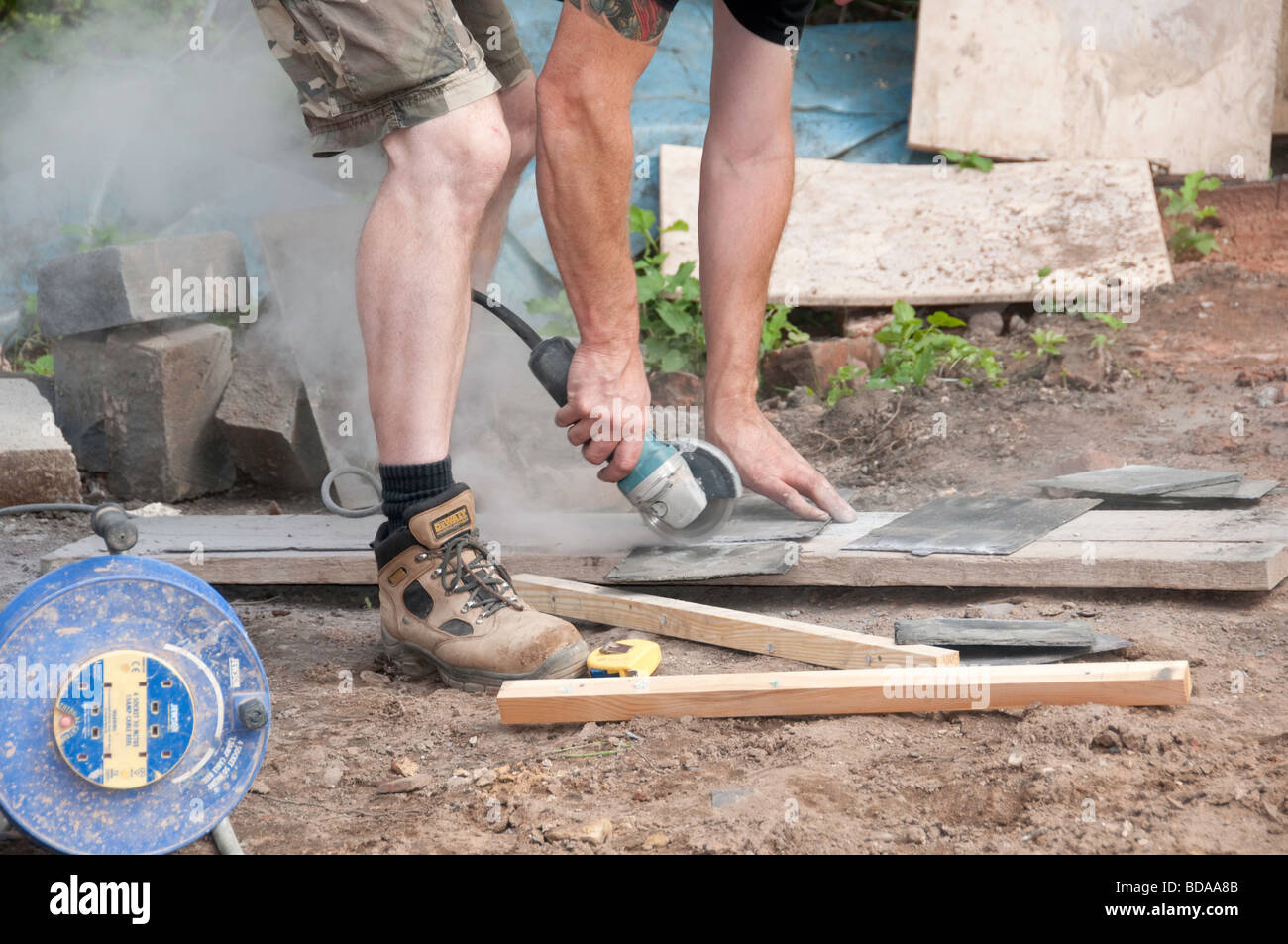 Reclaimed roofing tiles being cut with angle grinder - Stock Image