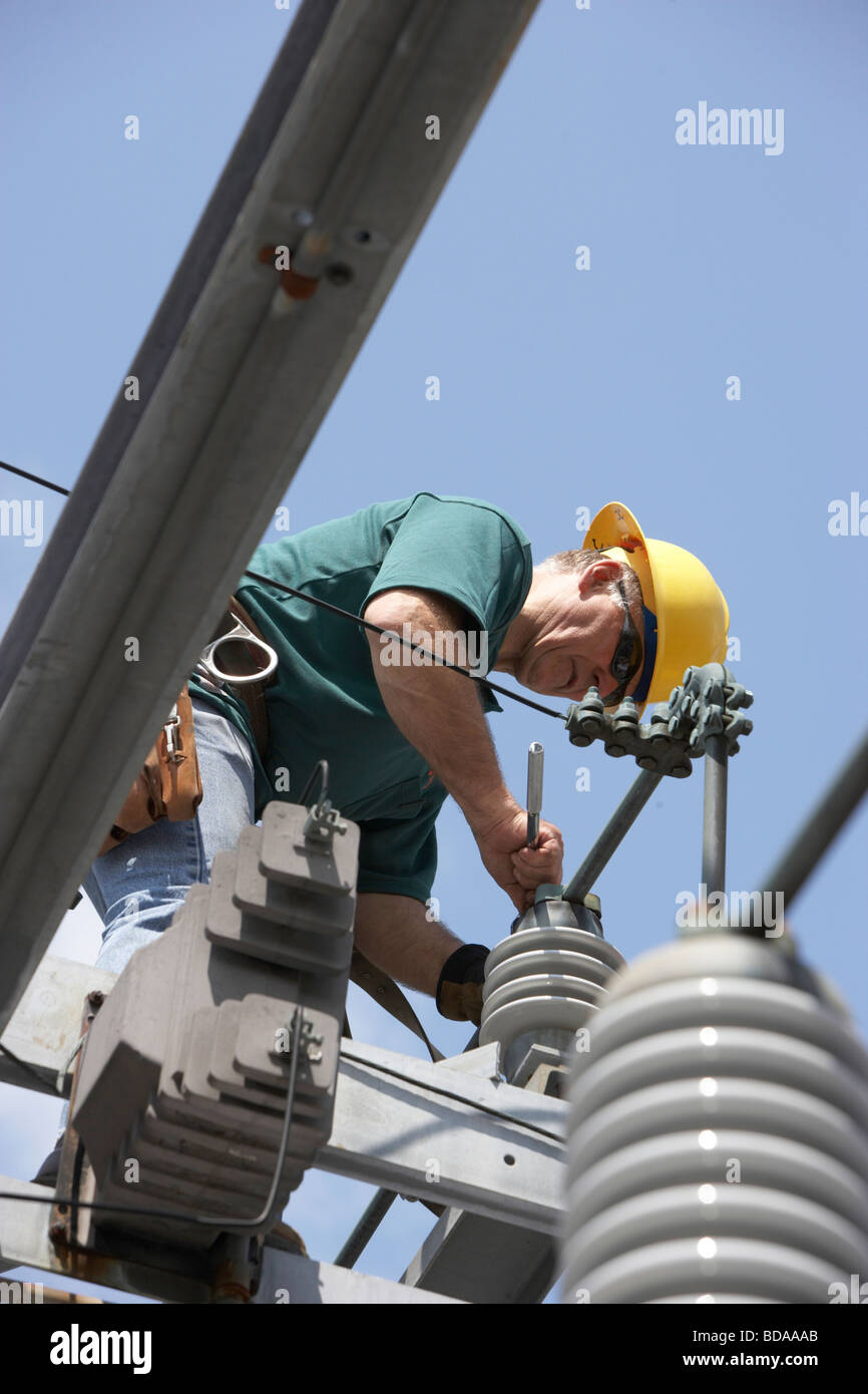 Utility workman wearing safety harness and hardhat installing new equipment on an electrical substation structure - Stock Image