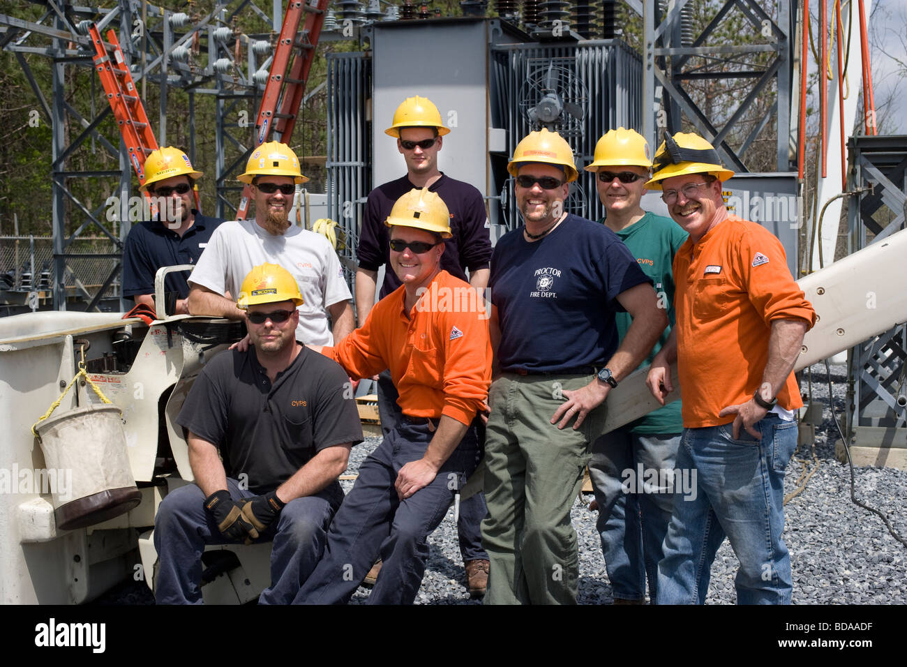 Electrical utility workmen posing for a group portrait - Stock Image