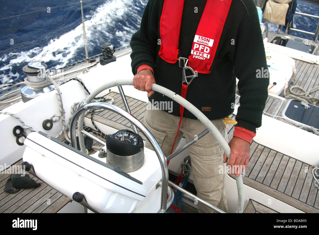 The helmsman on a modern yacht wearing a life jacket and harness - Stock  Image