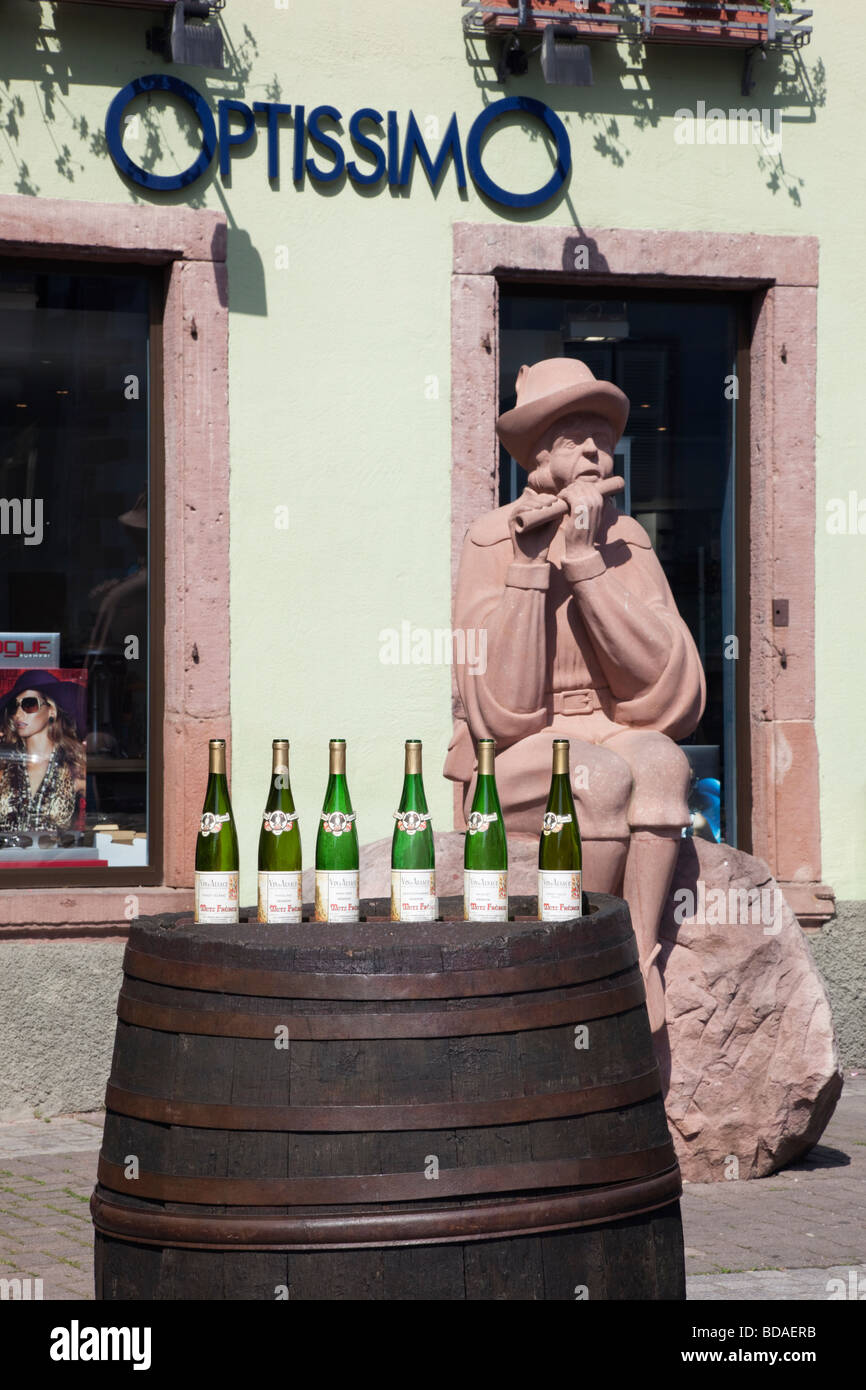 Ribeauville Alsace Haut Rhin France Display of wine bottles on an old wooden barrel beside a statue on Alsatian - Stock Image