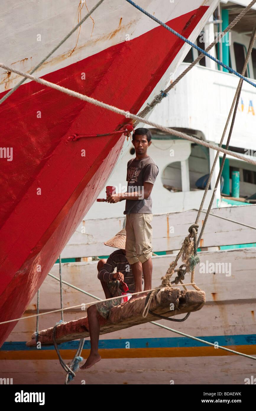 Indonesia Java Jakarta old Batavia Sunda Kelapa men painting traditional wooden sailing cargo boat - Stock Image