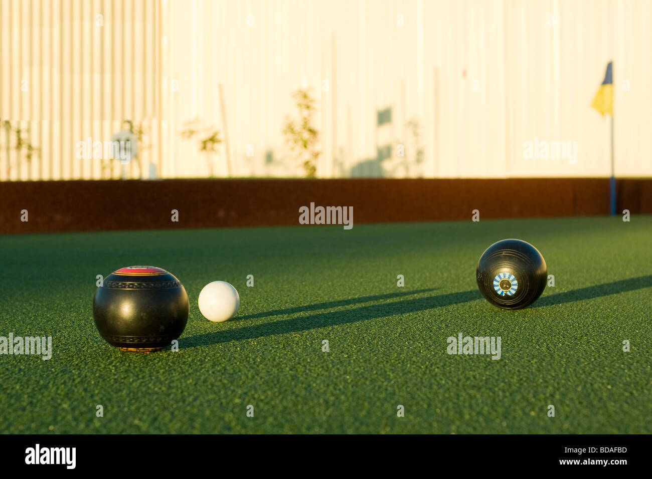 Lawn bowls in late afternoon sun shadows - Stock Image