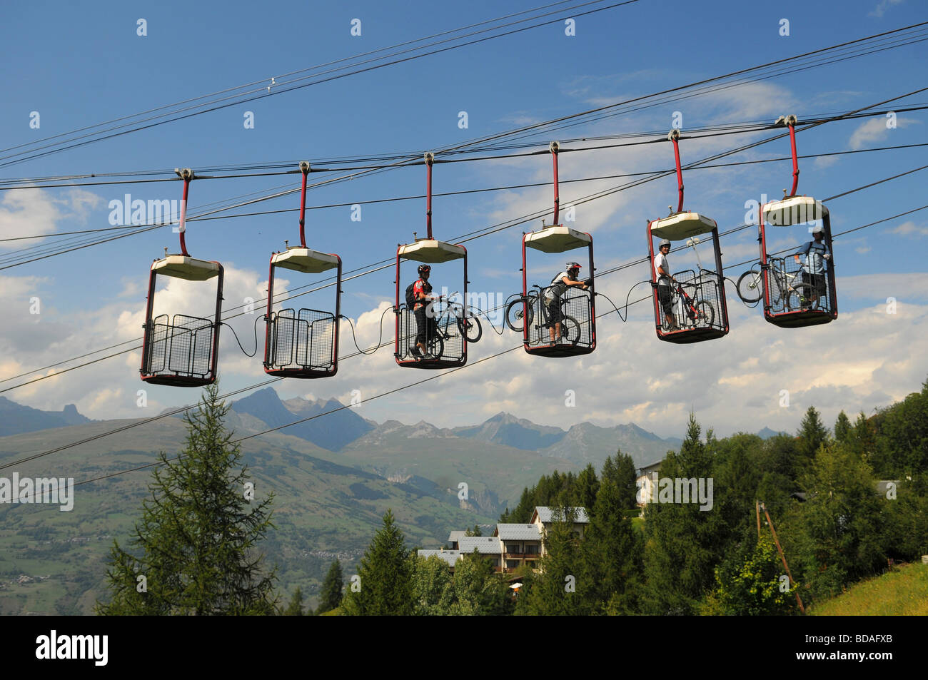 A group of mountain bikers use an unusual ski lift in Les Arcs in the French Alps - Stock Image