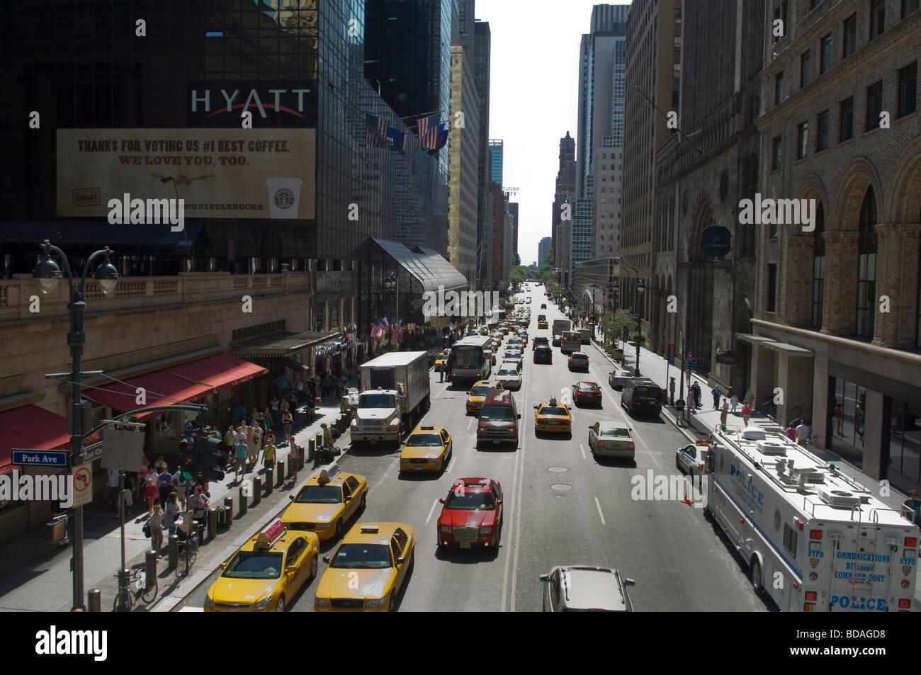 Traffic on E42 St and advertising for Starbucks outside the Grand Hyatt Hotel in New York - Stock Image