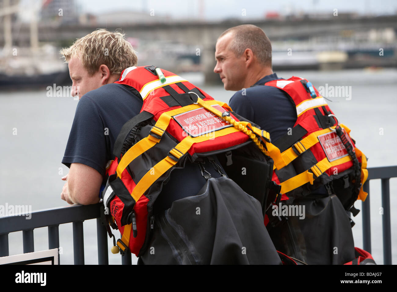 two members of the northern ireland fire and rescue service water rescue team watch proceedings at an event - Stock Image