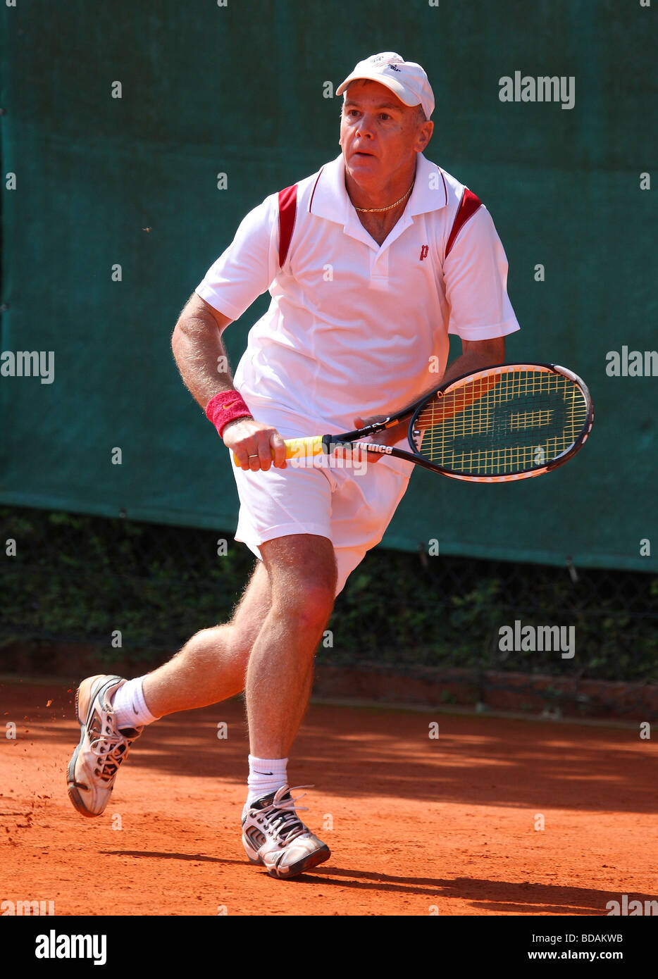 Elderly man playing a backhand at a tennis tournament - Stock Image