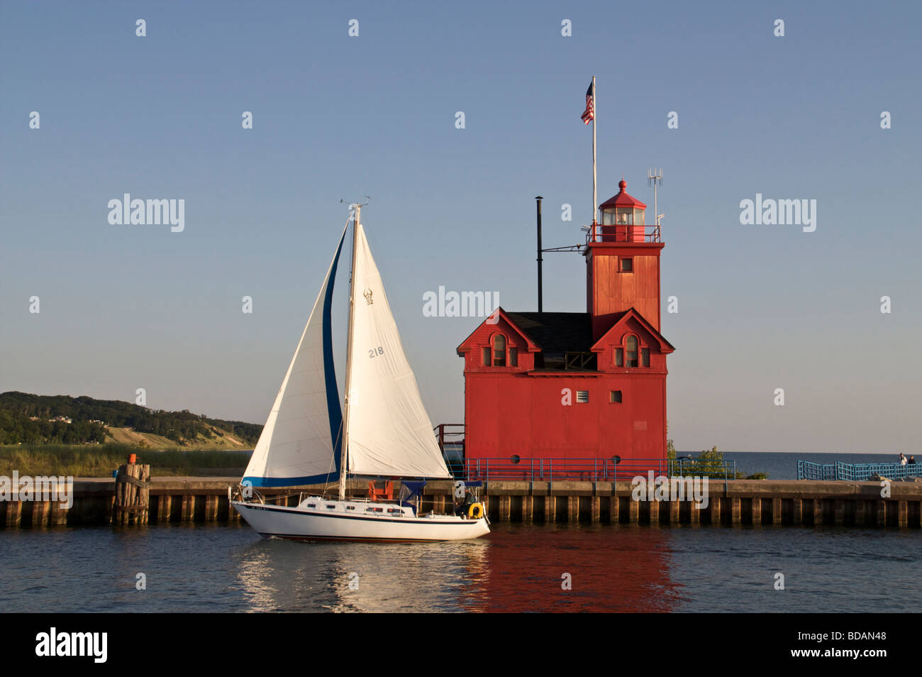 Sailboat entering harbor channel Holland State Park Michigan passing Big Red the entry lighthouse - Stock Image