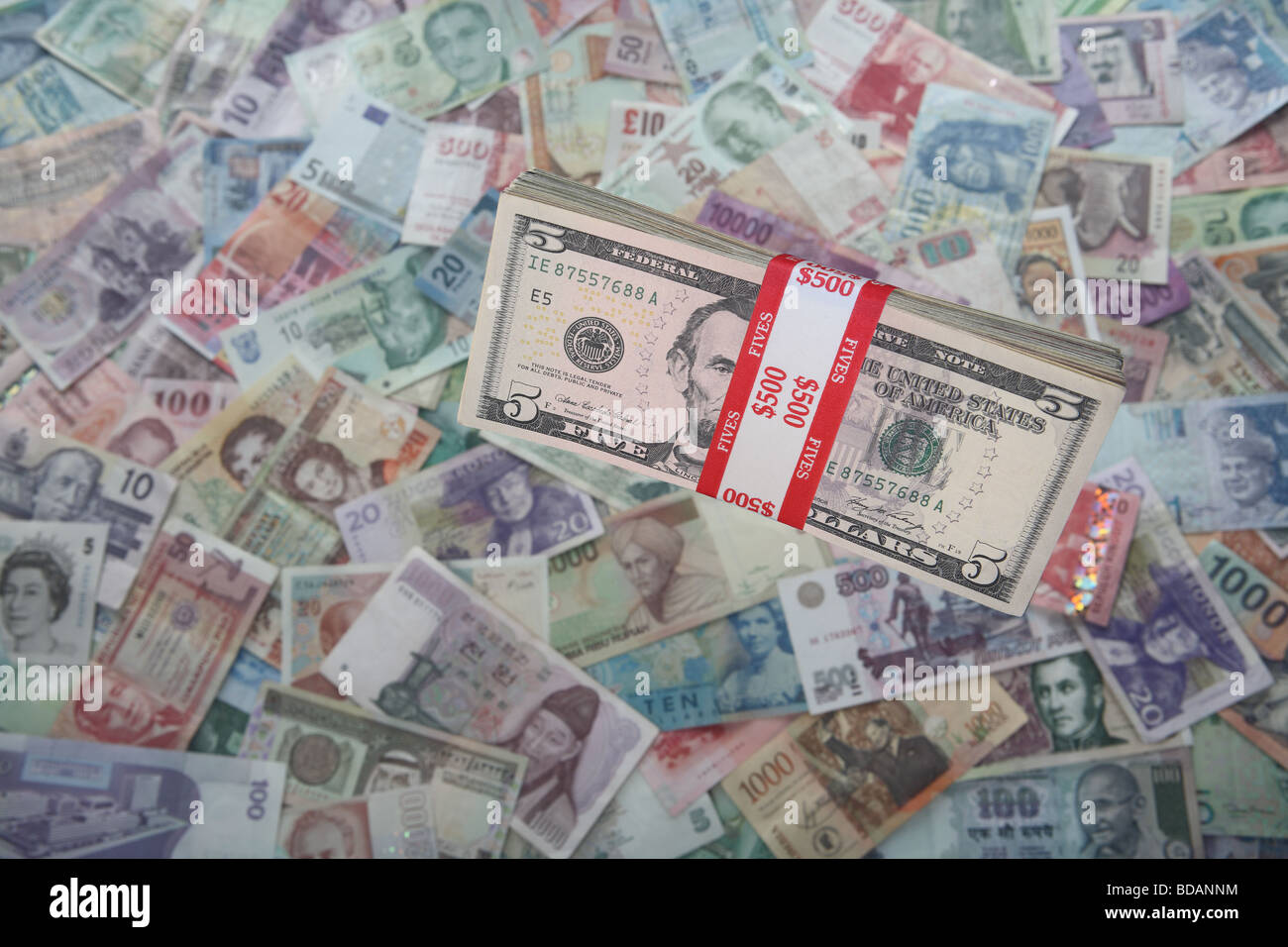 A bundled stack of five dollar bills on a soft background of international currencies - Stock Image