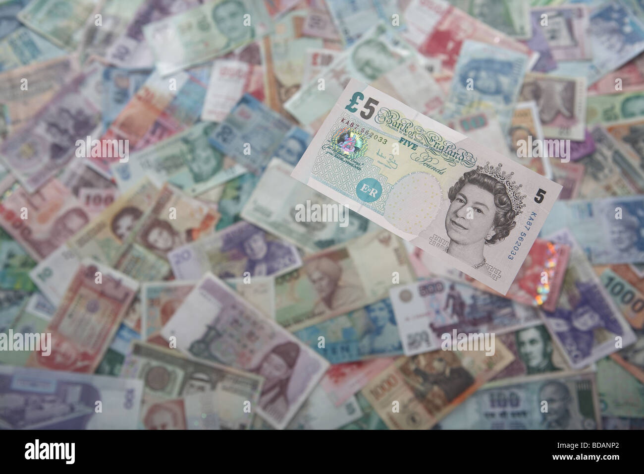 A British Five British Pound note on a soft background of international currencies - Stock Image