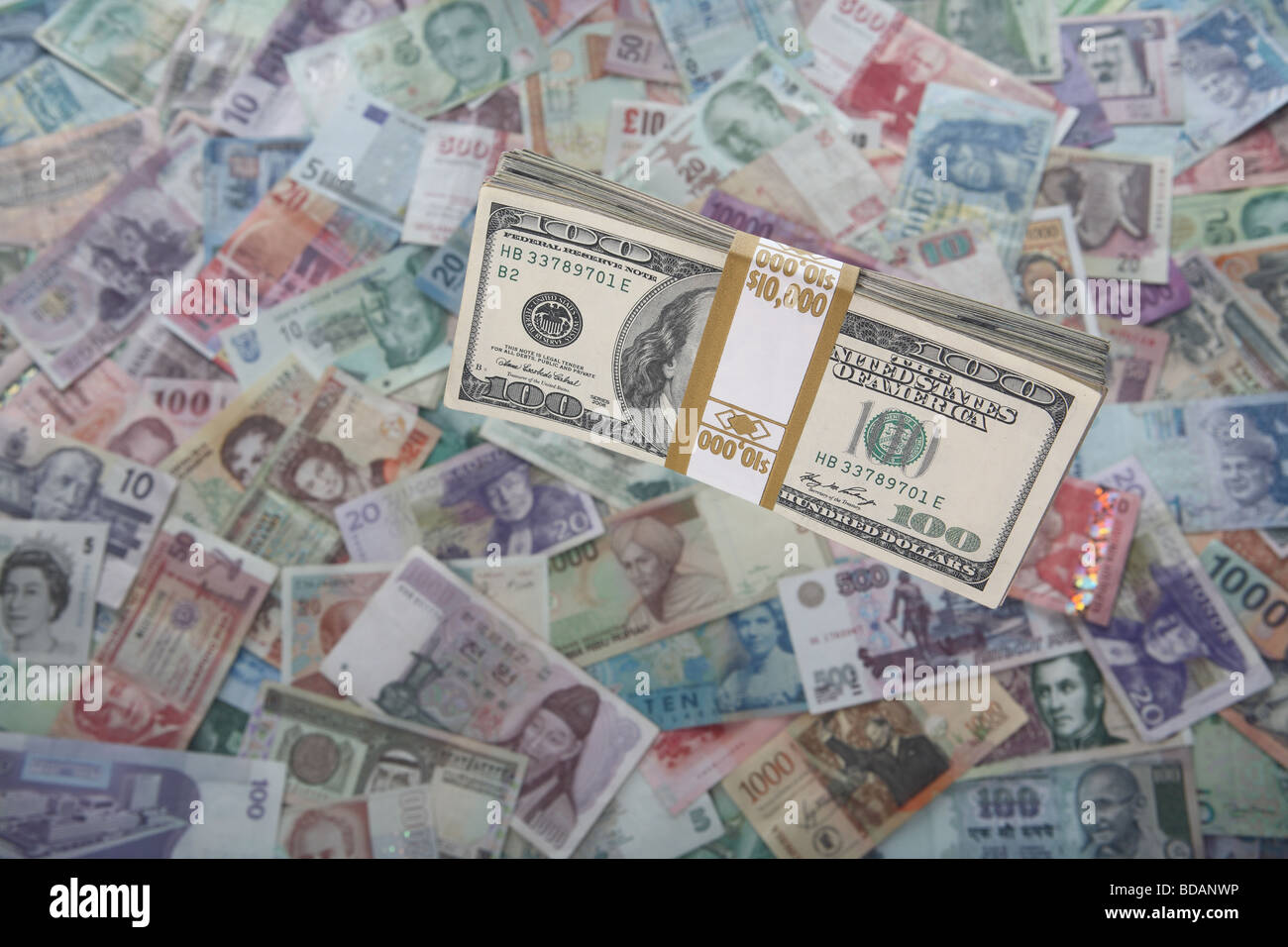A bundled stack of hundred dollar bills on a soft background of international currencies - Stock Image