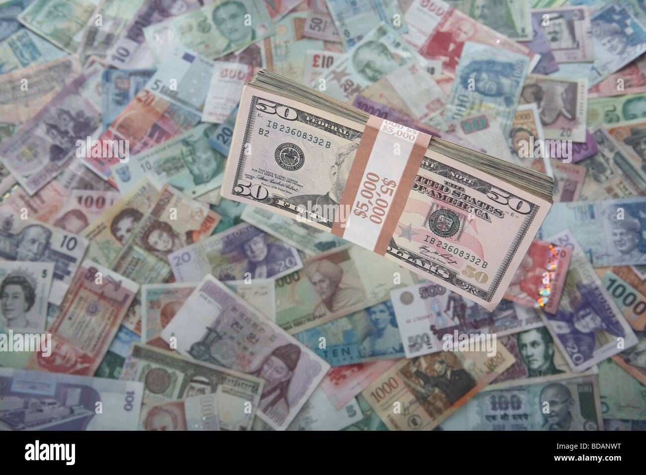 A bundled stack of fifty dollar bills on a soft background of international currencies - Stock Image