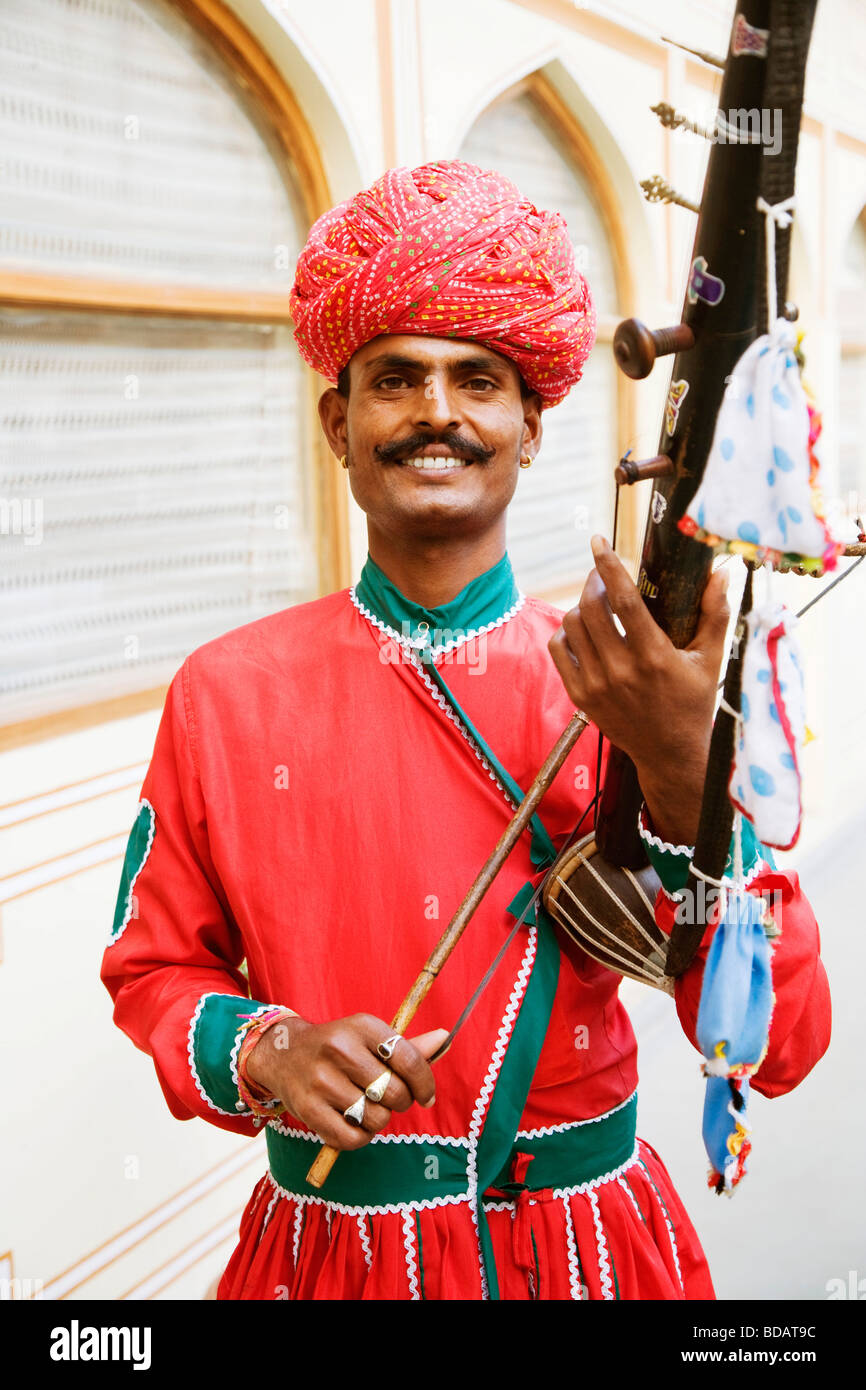 Mid adult man playing sarangi in a palace, City Palace, Jaipur, Rajasthan, India - Stock Image