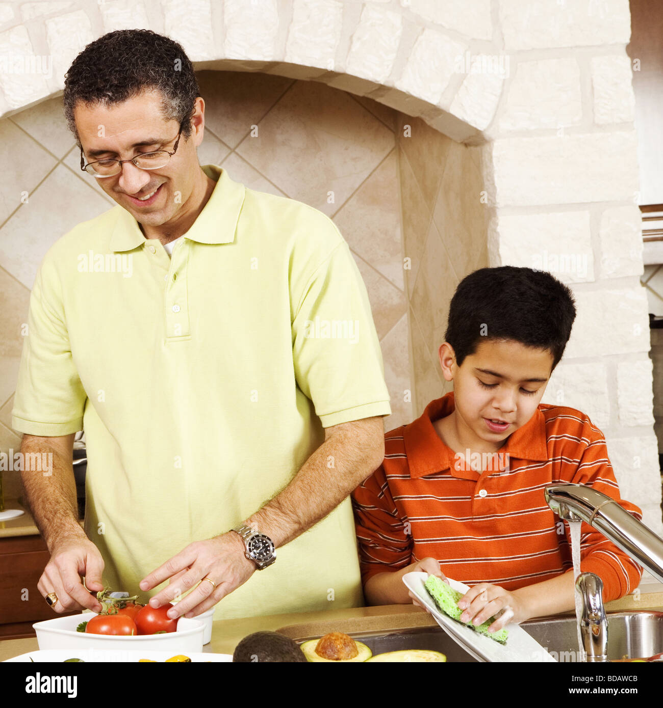Boy working in a kitchen with his father and grandfather - Stock Image