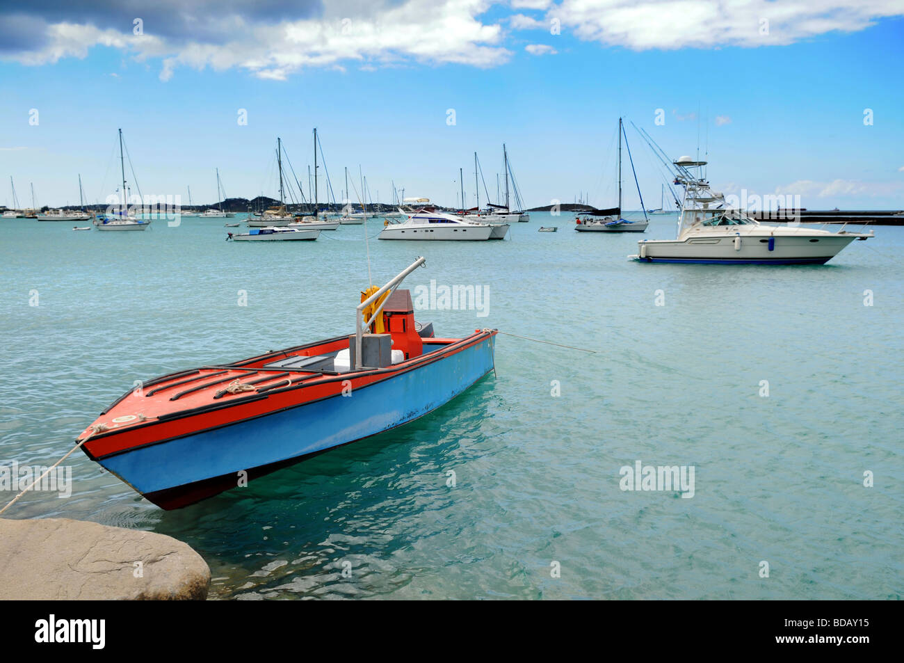 Old boat moored in Saint Martin in the Caribbean with modern boats in the background - Stock Image